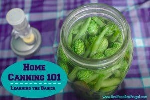 home canning guide featured image with a jar of pickles on a purple and white checkered tablecloth