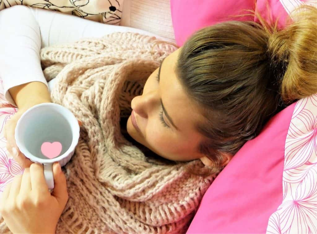 woman in bed with a cup of tea and a scarf