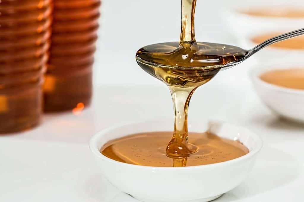 honey dripping into a teaspoon