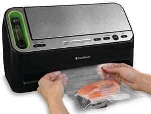 Black and Silver food sealer system shown sealing fresh salmon
