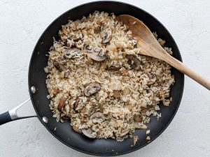 Brown rice, onions and mushrooms in a frying pan
