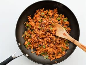 shredded sweet potatoes in pan with peppers and onions