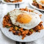Fried egg over sweet potato hash served on a white plate and tablecloth - serves 4.