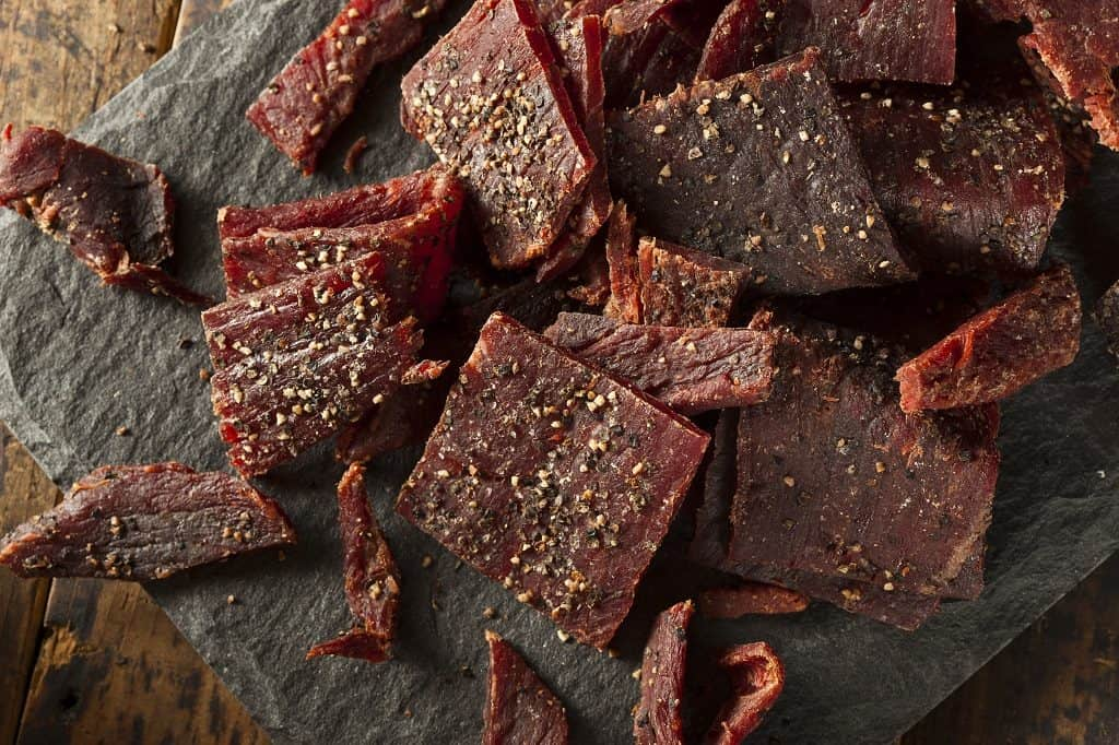 Homemade slices of beef jerky on a serving platter.