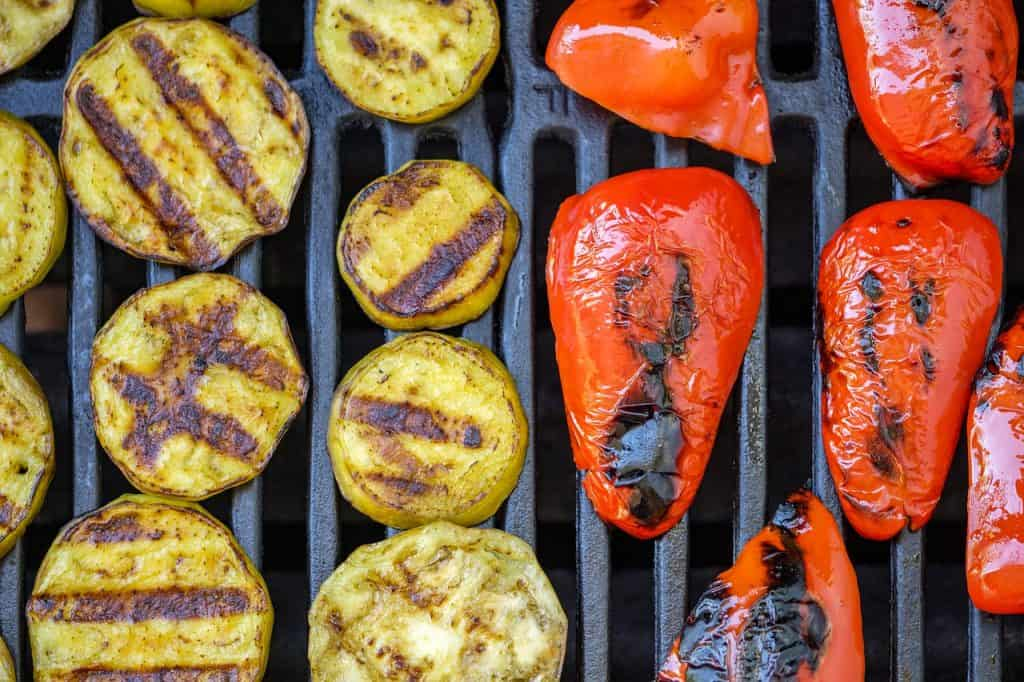 sliced eggplants and red peppers on the grill