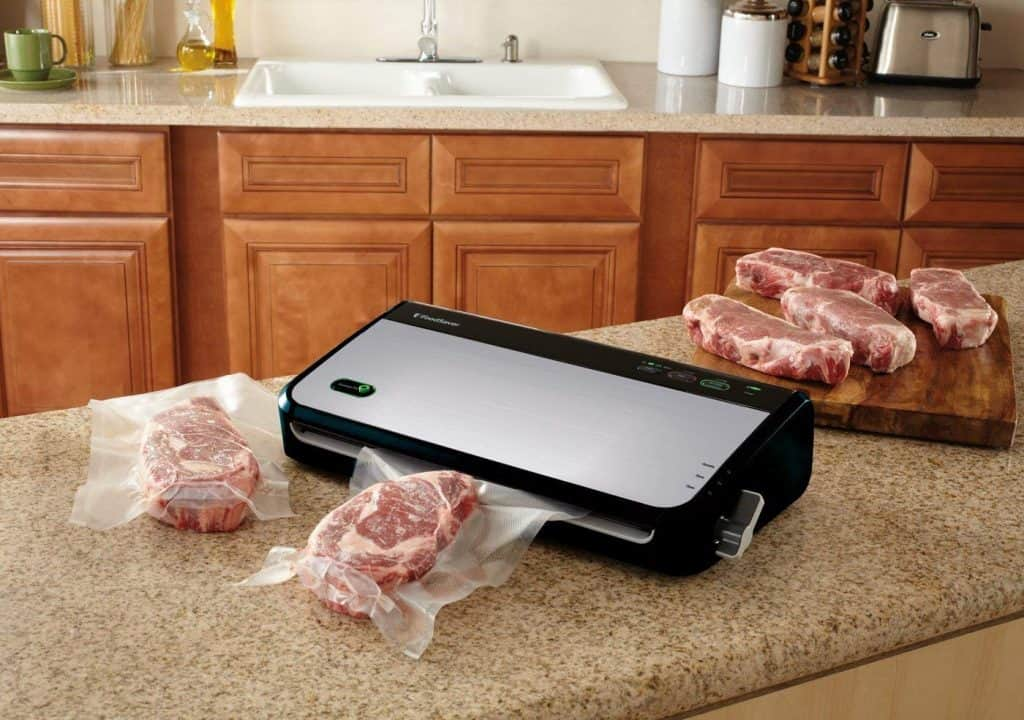 vacuuming fresh steaks on a countertop