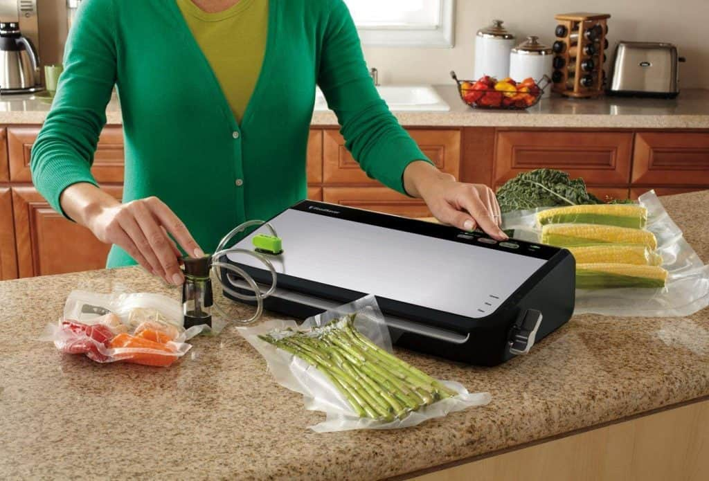 sealing bags of corn asparagus and fresh fish with the handheld attachment