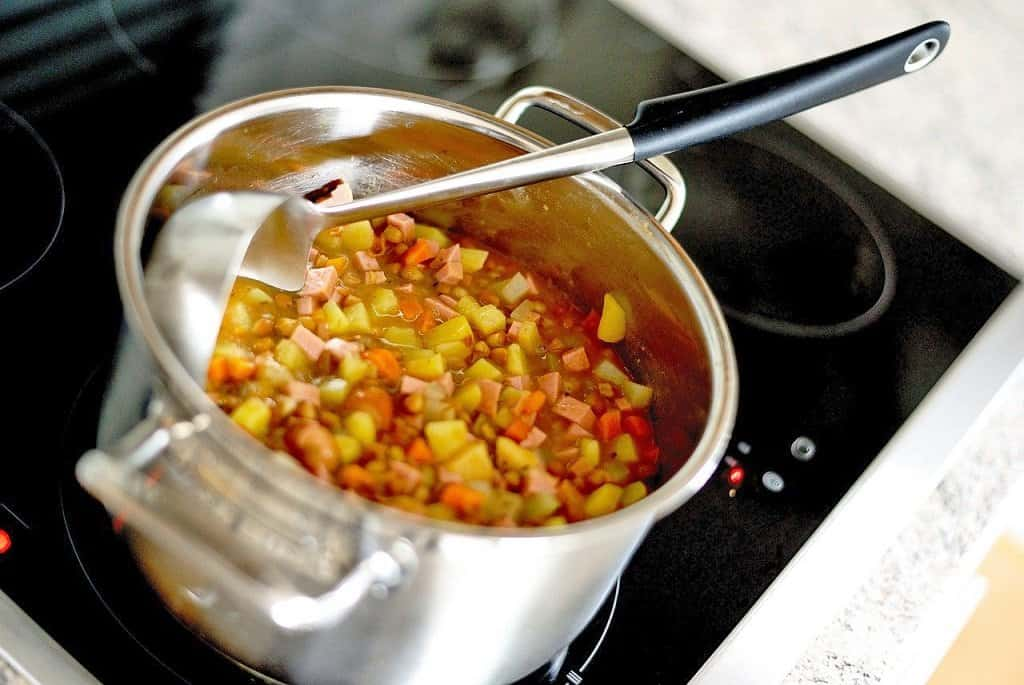 pot of soup cooking on the stovetop with a ladel