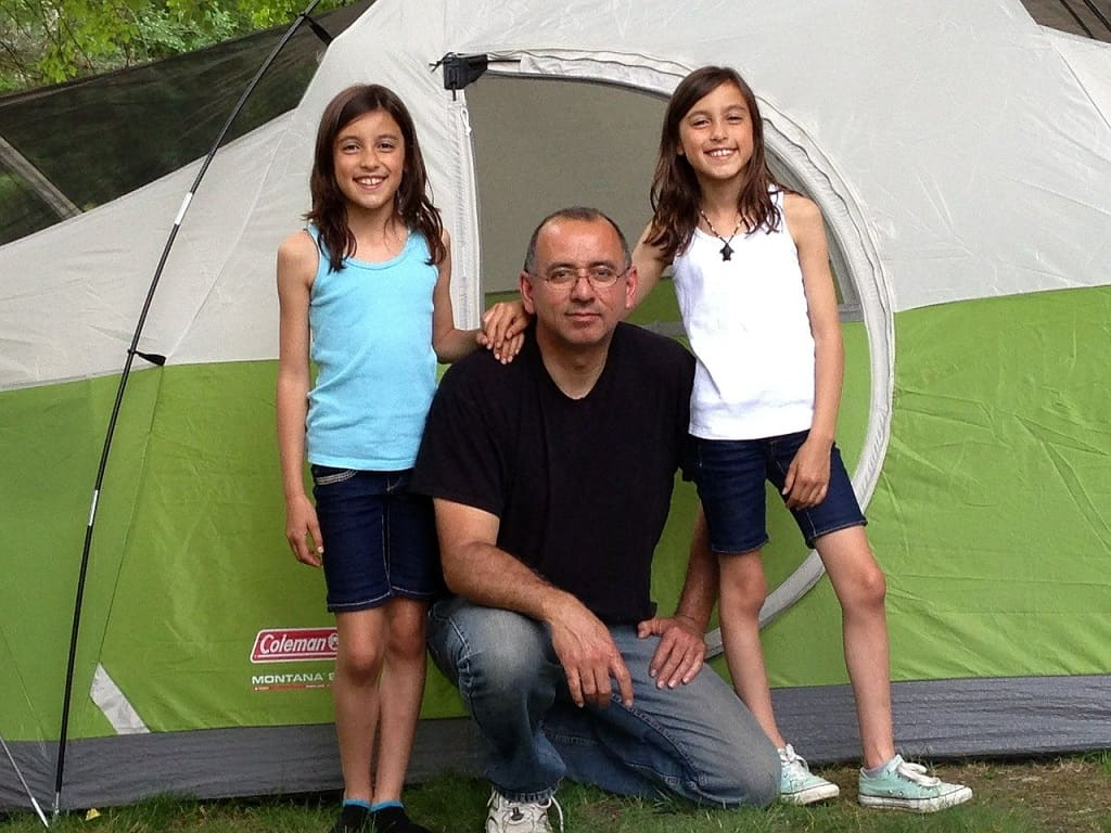 father and his 2 daughters outside a green and white tent