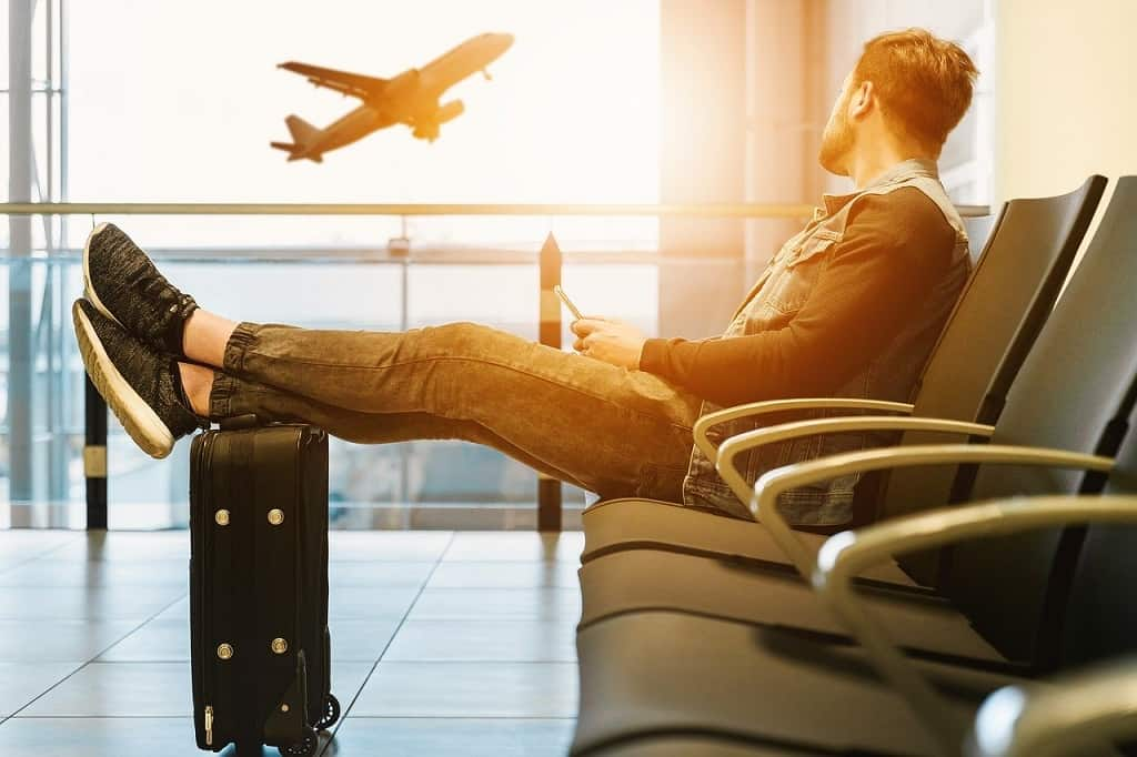 man waiting at the airport watching the plane take off to get a great deal on an airline ticket