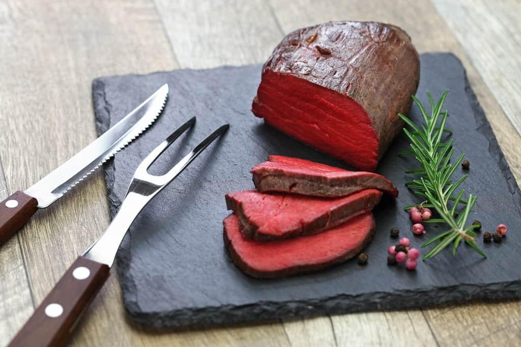 Cooked venison steak sliced on a serving platter