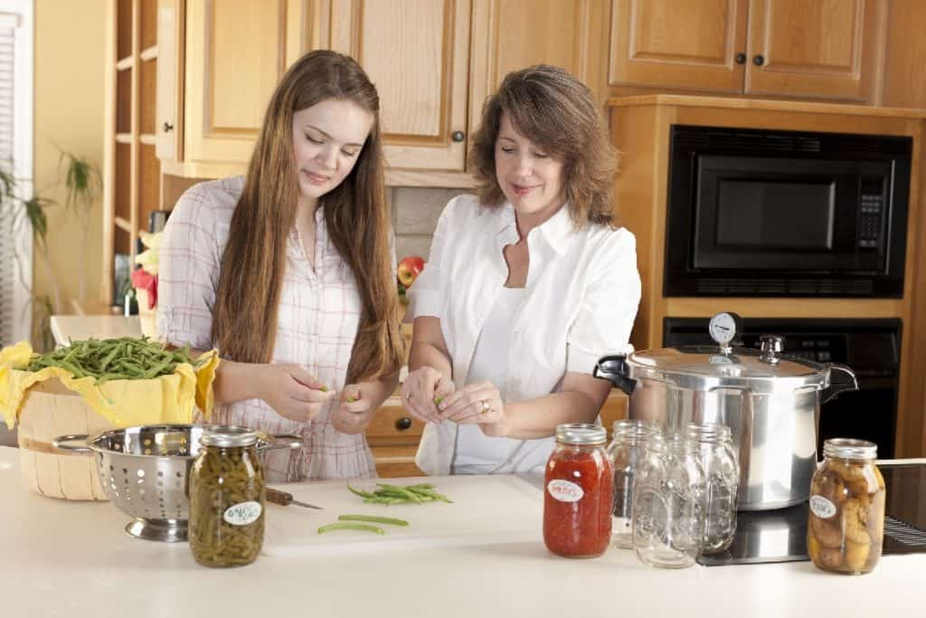 mother and daughter using pressure canner to preserve vegetables