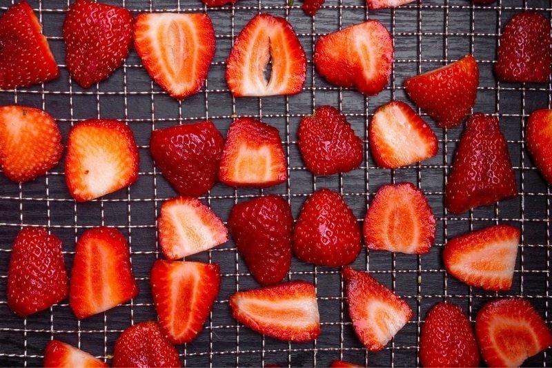 sliced strawberries on a dehydrator tray