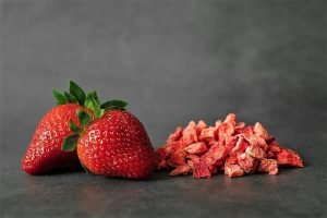 two fresh strawberries with a pile of dehydrated fruit next to it