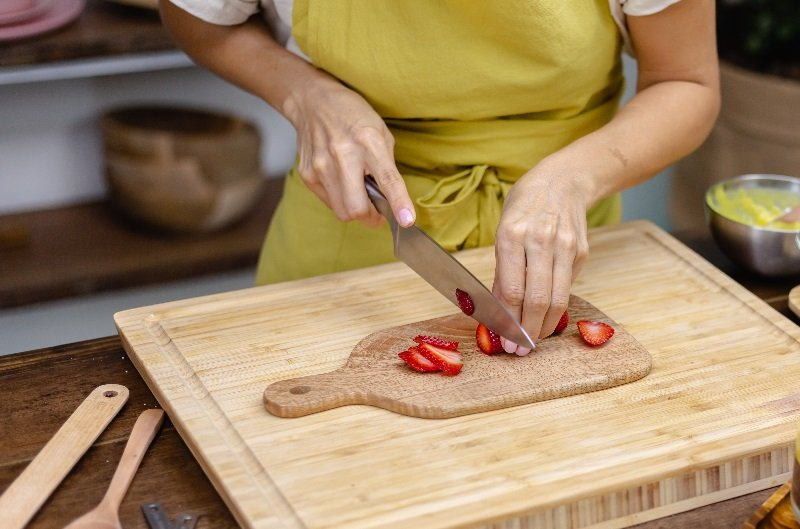 slicing strawberries on a wooden cutting board